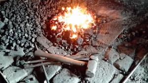 Schmiedefeuer mit Hammer und Zange